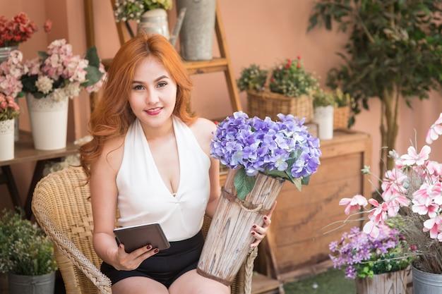 Sourire beau commerce femme vérifier l'ordre dans le magasin de fleurs