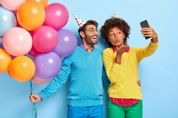 Sourire beau jeune couple lors d'une fête posant avec des ballons