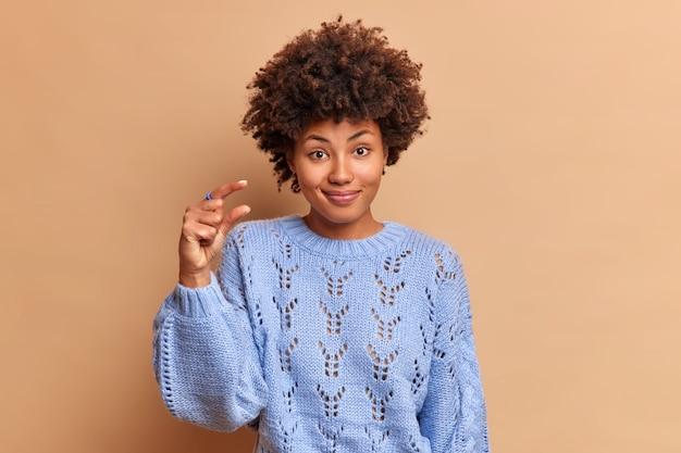Sourire beau jeune femme aux cheveux bouclés fait le geste de taille avec les doigts façonne quelque chose de petit demande pas trop porte pull décontracté isolé sur mur de studio brun