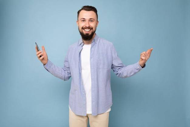 Sourire beau jeune homme mal rasé brune avec barbe portant élégant t-shirt blanc et chemise bleue isolé sur fond bleu avec un espace vide tenant en main un regardant la caméra.