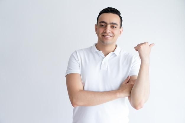 Sourire beau jeune homme pointant le pouce de côté. guy recommande quelque chose.