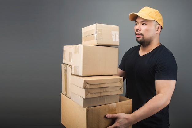 Sourire beau livreur asiatique portant casquette, donnant et transportant des colis, boîte en carton, journée de déménagement et concept de livraison express