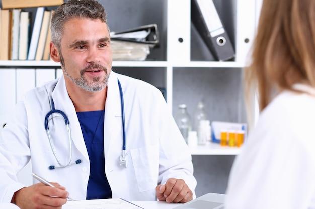 Sourire beau médecin mature communiquer avec le patient
