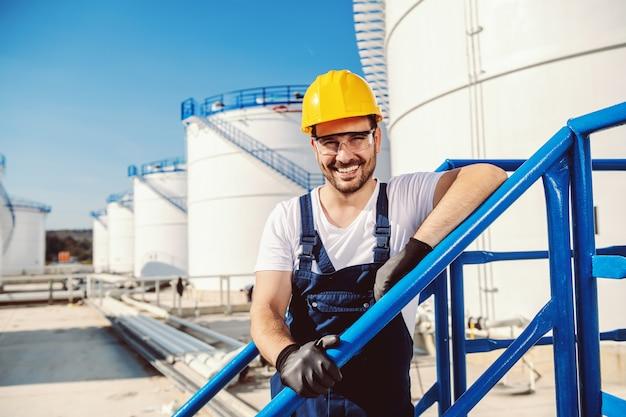 Sourire beau travailleur caucasien dans l'ensemble et avec un casque sur la tête appuyé sur la balustrade. production d'huile.