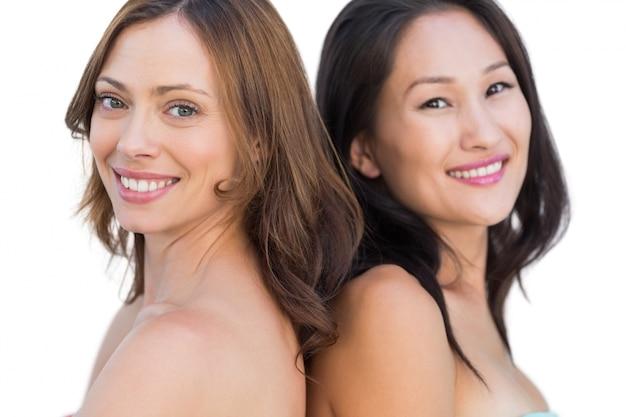 Sourire de beaux modèles nus posant dos à dos