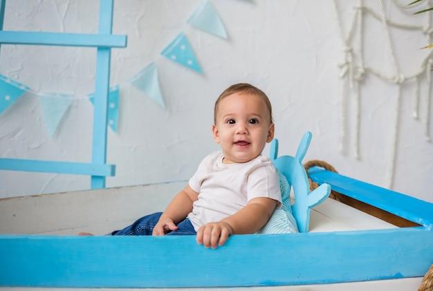 Sourire bébé garçon et est assis dans un bateau en bois