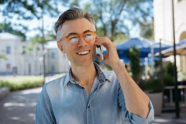 Sourire bel homme d'affaires à l'aide de smartphone