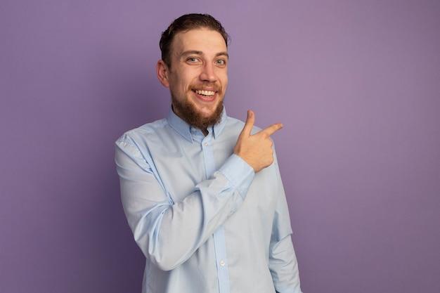 Sourire bel homme blond pointe sur le côté isolé sur mur violet
