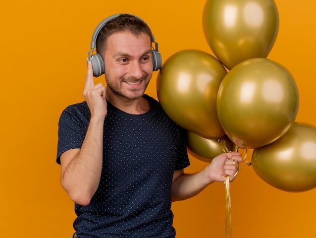 Sourire bel homme caucasien sur les écouteurs détient des ballons d'hélium à côté isolé sur fond orange avec copie espace