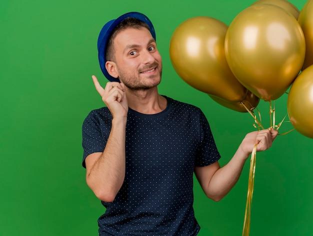 Sourire bel homme caucasien portant chapeau de fête bleu détient des ballons d'hélium et pointe vers le haut isolé sur fond vert avec espace copie