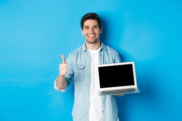 Sourire bel homme montrant l'écran de l'ordinateur portable et le pouce vers le haut