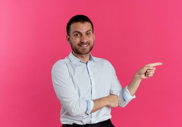 Sourire bel homme pointe sur le côté isolé sur un mur rose
