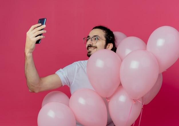 Sourire bel homme portant des lunettes tenant des ballons et prendre un selfie isolé sur rose