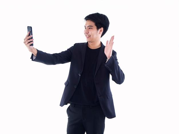 Sourire bel homme avec smartphone ayant appel vidéo et agitant la main en se tenant debout sur blanc