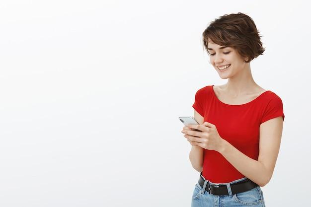 Sourire belle femme à l'aide de l'application de téléphone mobile, lire le message avec un visage heureux