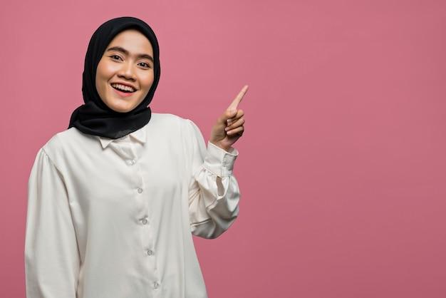 Sourire belle femme asiatique pointant vers un espace vide