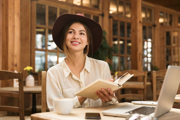 Sourire belle femme au chapeau assis à la table de café à l'intérieur