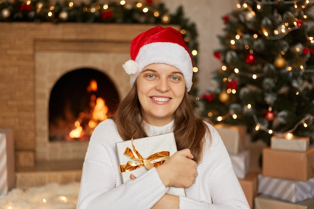 Sourire belle femme avec boîte-cadeau en mains posant à l'intérieur avec arbre de noël et cheminée