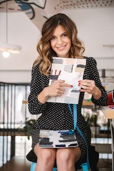 Sourire belle femme de couturière travaillant à l'atelier, en choisissant des matériaux