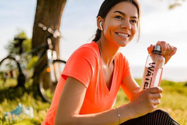 Sourire belle femme eau potable en bouteille faire du sport le matin dans le parc