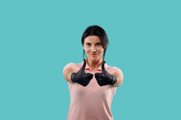 Sourire belle femme portant des gants de protection en latex noir montrant les pouces vers le haut. portrait isolé sur fond bleu