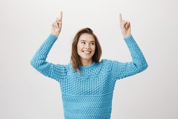 Sourire belle femme en pull pointant les doigts vers le haut