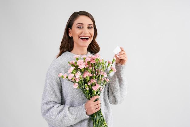 Sourire, belle femme tenant un bouquet de fleurs et une carte de voeux