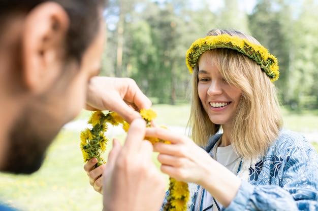 Sourire belle fille aider son petit ami pendant qu'ils font une couronne de pissenlit à l'extérieur
