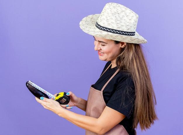 Sourire belle fille de jardinier en uniforme portant chapeau de jardinage mesurant l'aubergine avec un ruban à mesurer isolé sur fond bleu