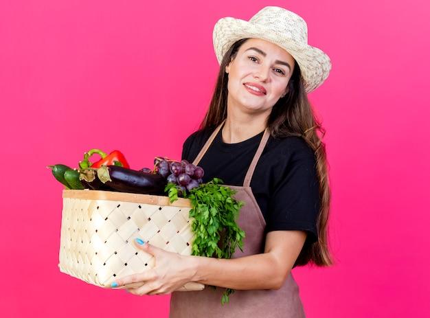 Sourire belle fille de jardinier en uniforme portant un chapeau de jardinage tenant un panier de légumes isolé sur fond rose