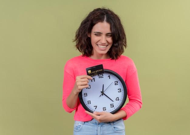 Sourire belle jeune femme tenant la carte et l'horloge sur le mur vert isolé avec espace copie