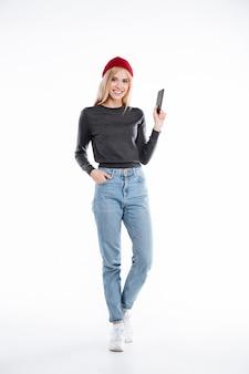 Sourire, blond, jeune femme, dans, chapeau, standig, et, tenue, vide, téléphone portable