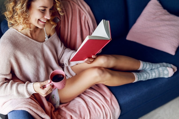 Sourire blonde belle femme reposante sur le canapé à la maison. pull en maille rose, chaussettes chaudes. livre de lecture et tenant une tasse de café.