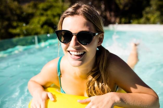 Sourire blonde avec gonflable dans la piscine