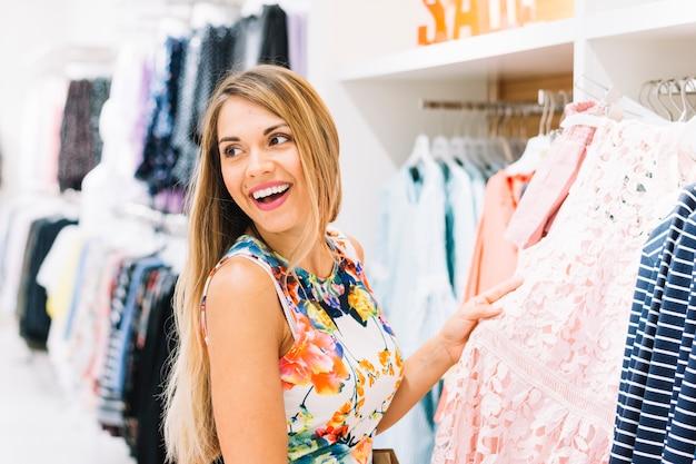 Sourire blonde jeune femme tenant la robe de rack à la recherche de suite