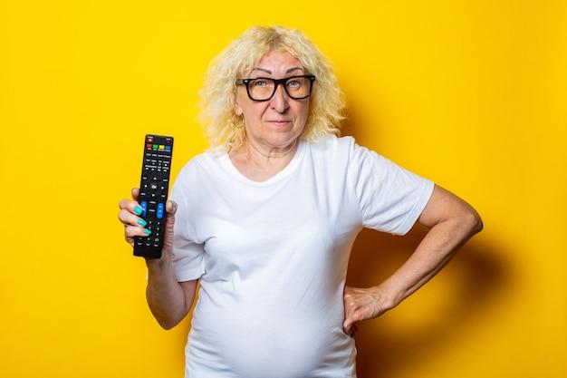 Sourire blonde vieille femme à lunettes tenant la télécommande