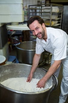 Sourire boulanger la farine de mélange