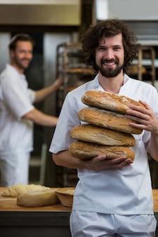 Sourire boulanger portant pile de pains cuits