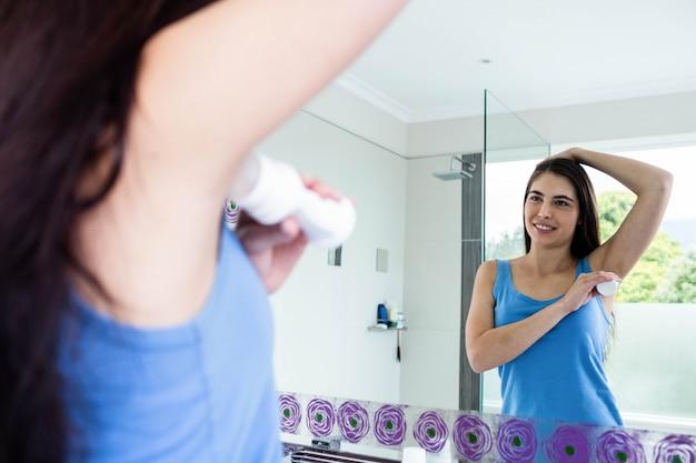 Sourire brune mettant un déodorant sur son aisselle dans la salle de bain