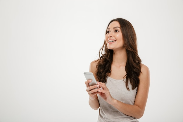 Sourire, brunette, femme, tenue, smartphone, regarder, loin, gris