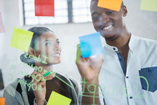 Sourire des collègues de travail écrivant sur des notes autocollantes
