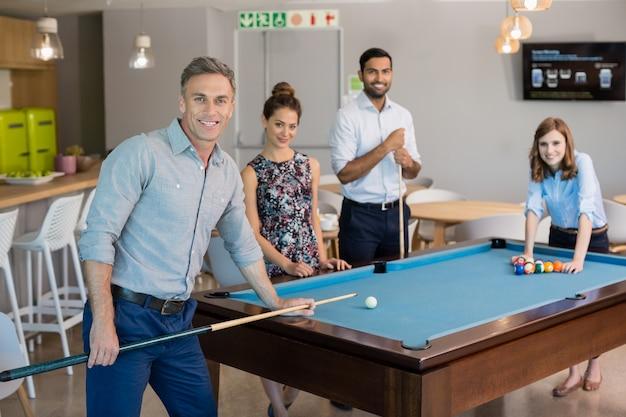 Sourire des collègues de travail jouant au billard dans l'espace de bureau