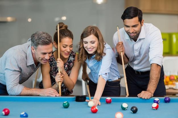 Sourire des collègues de travail jouant au billard
