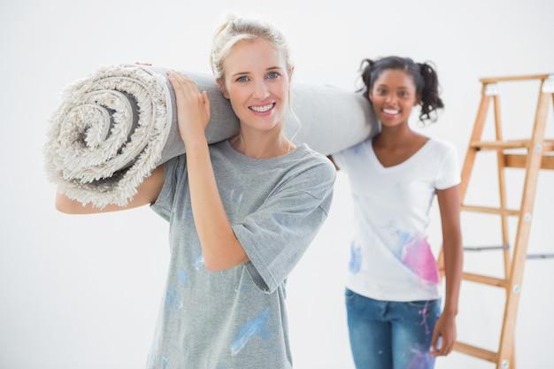Sourire de colocataires portant un tapis roulé