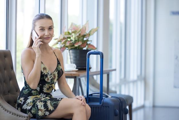 Sourire, confiant, femme moderne parlant par téléphone dans le hall de l'hôtel