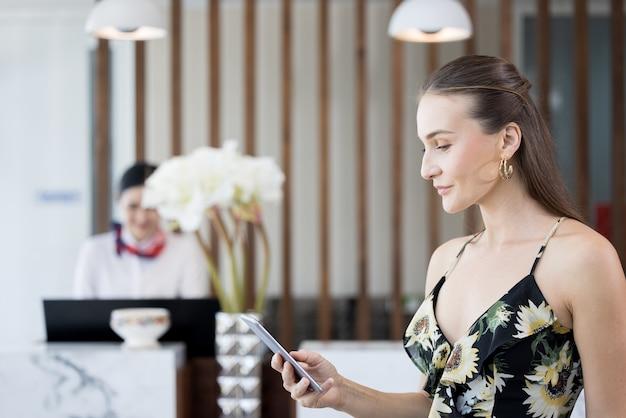 Sourire, confiant, femme moderne parlant et vérifiant les médias sociaux au téléphone mobile dans le hall de l'hôtel