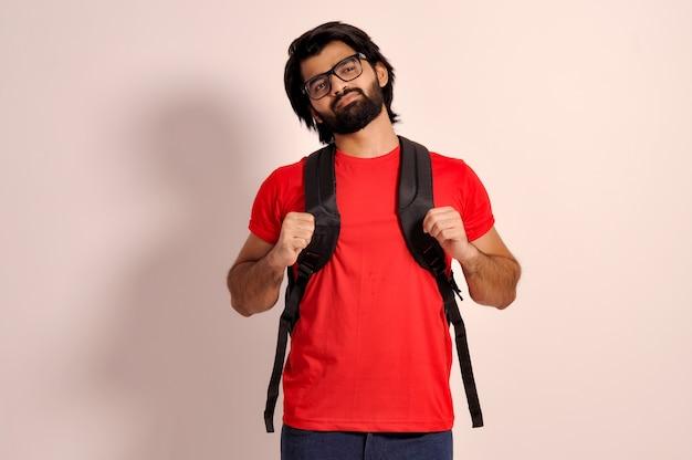 Sourire confiant jeune bel étudiant barbu tenir le sac à dos avec les deux mains en levant
