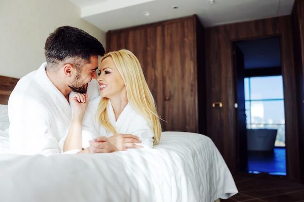 Sourire couple d'âge moyen amoureux allongé sur le ventre dans son lit et câlins. ils fêtent leur anniversaire à l'hôtel.