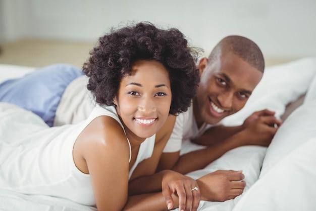 Sourire couple allongé sur le lit en regardant la caméra