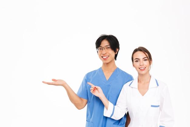 Sourire couple de médecins en uniforme debout isolé sur un mur blanc, pointant vers l'espace de copie